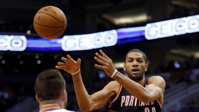 Portland Trail Blazers' Nicolas Batum (88) passes as Phoenix Suns' Miles Blumlee (22) looks on during the first half of an NBA basketball game, Wednesday, Nov. 27, 2013, in Phoenix