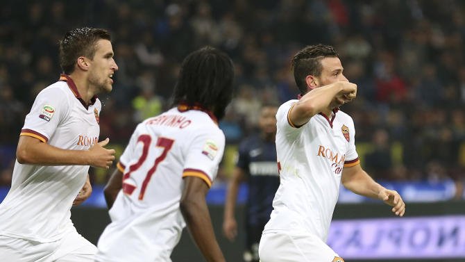 AS Roma midfielder Alessandro Florenzi, right, celebrates with his teammates Kevin Strootman, left, of the Netherlands, and Gervinho, of Ivory Cost, after scoring during the Serie A soccer match between Inter Milan and Roma at the San Siro stadium in Milan, Italy, Saturday, Oct. 5, 2013