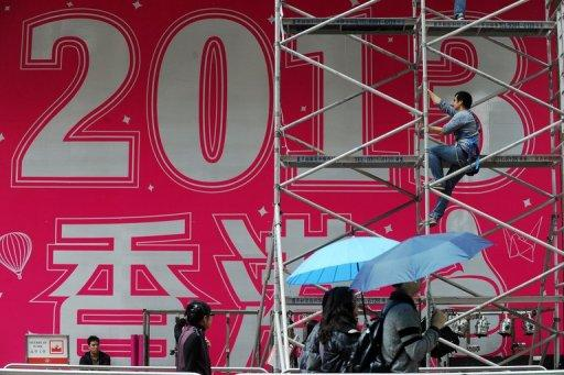 A worker prepares a promotional 2013 banner outside a shopping mall in Hong Kong on Saturday. As the clock strikes 12 on Monday, millions will pop champagne corks and light fireworks while others indulge in quirkier New Year's rituals like melting lead, leaping off chairs or gobbling grapes.