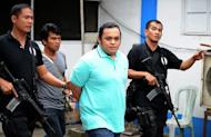 Policemen escort Sajid Anwar Ampatuan (centre) in police headquarters in Manila last year. A gun battle between soldiers and car passengers at a military checkpoint led to the arrest of a another suspect in the Philippines' worst political massacre when he was spotted among onlookers, an army spokesman said Sunday