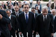 Greece's new Prime Minister Antonis Samaras (C) and Foreign minister Dimitris Avramopoulos (R), flanked by security and newly appointed ministers, arrive at the Greek parliament for their first cabinet meeting