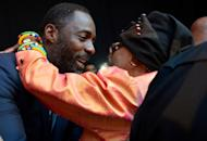 Nelson Mandela's second wife Winnie Madikizela–Mandela (R) and British actor Idris Elba hug each other as they attend the movie's premiere in Johannesburg on November 3, 2013