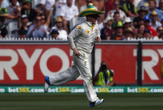 Australia's Rogers runs while wearing a hat that blew onto the ground, during the first day of the fourth Ashes cricket test against England at the Melbourne cricket ground