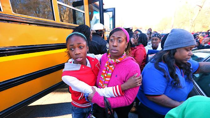 Mother and daughter embrace as Tiffany Myricle, 37, leads her daughter Xavia Denise Myricle away from her school bus when parents and children are reunited at Emmanuel Baptist Church after a shooting at an Price Middle school in Atlanta on Thursday, Jan. 31, 2013. A 14-year-old boy was wounded outside the school Thursday afternoon and a fellow student was in custody as a suspect, authorities said. No other students were hurt. (AP Photo/Atlanta Journal-Constitution, Curtis Compton)  MARIETTA DAILY OUT; GWINNETT DAILY POST OUT; LOCAL TV OUT; WXIA-TV OUT; WGCL-TV OUT