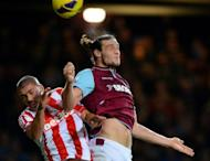 West Ham United's English midfielder Andy Carroll (R) jumps for the ball against Stoke City's Irish forward Jon Walters (L) during the English Premier League football match between West Ham and Stoke City at the Boleyn Ground, Upton Park, in East London, England. The match ended in a 1-1 draw