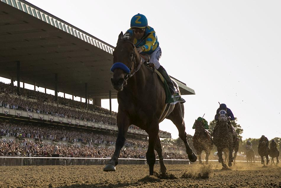 Jockey Victor Espinoza, aboard American Pharoah, passes the finish line to win the 147th running of the Belmont Stakes as well as the Triple Crown, in Elmont, New York