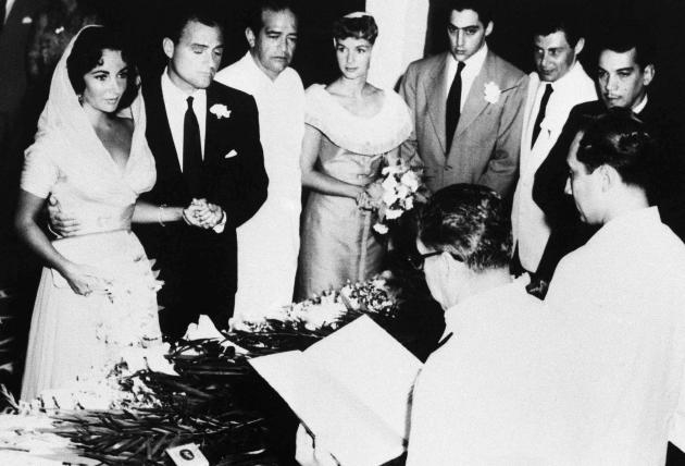 FILE - In this Feb. 3, 1957 file photo, actress Elizabeth Taylor and producer Mike Todd holds hands during their civil service ceremony in Acapulco, Mexico. The late Mexican comedian and actor Mario M