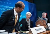 International Monetary Fund (IMF) Managing Director Christine Lagarde (C) and Singapore Finance Minister and International Monetary and Financial Committee (IMFC) chair Tharman Shanmugaratnam (L) take their seats for a G20 press conference at the IMF/World Bank Annual Spring Meetings in Washington, April 20, . The IMF raised $430 billion in new funds for crisis intervention