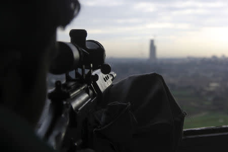 A rebel fighter aims his weapon at an area controlled by forces loyal to Syria's President Bashar al-Assad, from Al Waer
