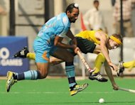 India's Sardar Singh (left) tackles Australian hockey player Matthew Swann during the men's hockey final match of the 2010 Commonwealth Games in New Delhi on October 14, 2010. A financial windfall awaits the world's leading field hockey stars when they play in a new Indian tournament next month on the lines of cricket's popular Indian Premier League
