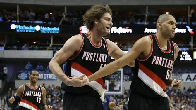 Portland Trail Blazers' LaMarcus Aldridge (12), Robin Lopez, center, and Nicolas Batum, right, of France, celebrate after a score by Batum against the Dallas Mavericks in the second half of an NBA basketball game, Saturday, Jan. 18, 2014, in Dallas. The Trail Blazers won 127-111