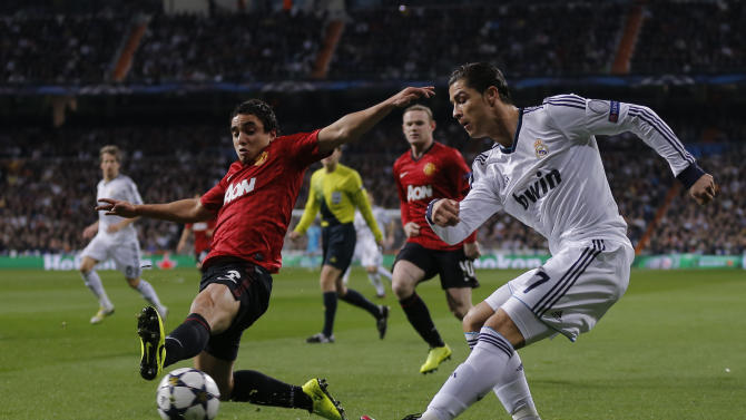 Real Madrid's Cristiano Ronaldo from Portugal, right, duels for the ball with Manchester United's Rafael during their Champions League round of 16 first leg soccer match at the Santiago Bernabeu stadium in Madrid, Wednesday Feb. 13, 2013. (AP Photo/Daniel Ochoa de Olza)