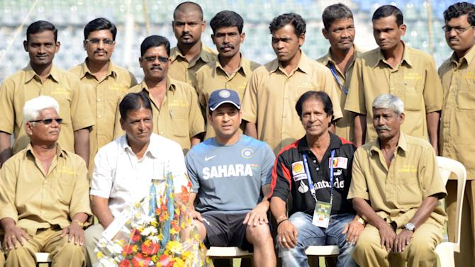 Master blaster Sachin Tendulkar with ground staffs members as they felicitated him ahead of his 200th and last test match at Wankhede Stadium in Mumbai on Nov.13, 2013. (Photo: Sandeep Mahankaal/IANS)
