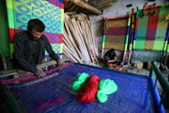 A Pakistani vendor weaves a cot with nylon threads at his shop in Peshawar, Pakistan on Monday, Nov. 14, 2011. (AP Photo/Mohammad Sajjad)