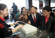 Pyo Hyun-Myung (2nd R), president of the Personal Customer Group at KT Corp, explains Apple's new iPad to the first customer in line, at a branch of KT, a Korean distributor of iPhones and iPads, in Seoul, on April 20. The new iPad went on sale in tech-savvy South Korea, about one month after it made its international debut