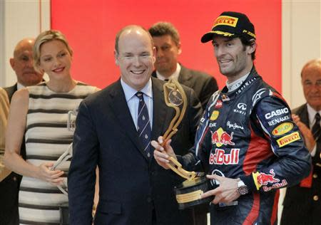 Red Bull Formula One driver Webber of Australia holds his trophy next to Prince Albert II and Princess Charlene of Monaco after winning the Monaco F1 Grand Prix