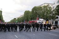 French riot police walk up the Avenue des Champs-Elysees in central Paris in May 25, 2013. Fifty opponents of gay marriage were arrested in central Paris late Saturday, police said, on the eve of a major protest against a new French law allowing homosexual couples to formally tie the knot