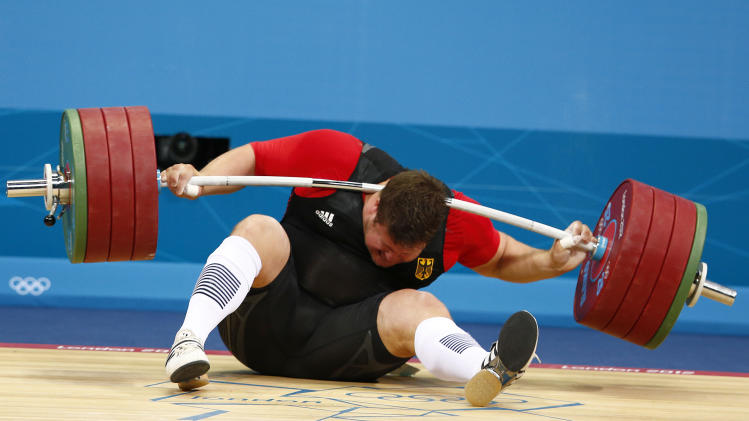 Germany's Matthias Steiner is injured while his weights fall during the men's  105kg Group A snatch weightlifting competition during the London 2012 Olympic Games