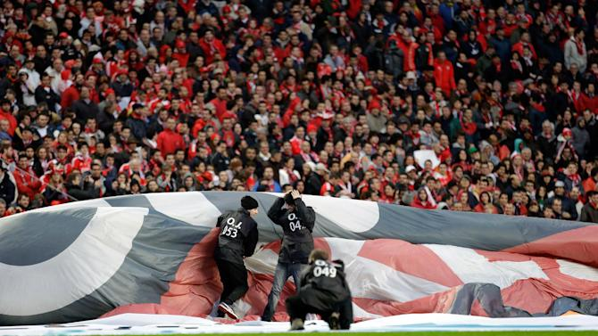 Workers holding an advertising banner struggle with the wind before the start of the Portuguese league soccer match between Benfica and Sporting Sunday, Feb. 9 2014, at Benfica's Luz stadium in Lisbon. Strong winds damaged the stadium roof before kick off and debris fell on the pitch and stands. It was decided the match should be postponed for safety reasons