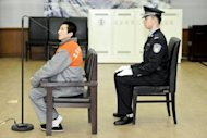 Policeman guards a 27-year-old man suspected of stealing several items from the Forbidden City, in a rare theft at China's ancient imperial palace, during his trial in Beijing, in February. Shi Baikui was on Monday sentenced to 13 years in jail for the theft