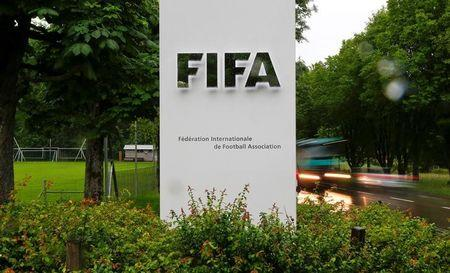 Cars drive past a logo in front of FIFA's headquarters in Zurich