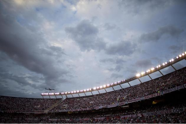 A plane flies over River Plate's stadium as fans cheer their team during an Argentine league soccer match against Velez Sarsfield in Buenos Aires, Argentina, Sunday, April 20, 2014