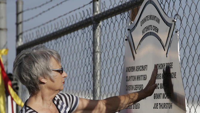 Georgia Johnson, of Prescott, Ariz., pays her respects at a plaque honoring 19 firefighters killed battling a wildfire near Yarnell, Ariz., Sunday outside the Granite Mountain Interagency Hotshot Crew fire station, Tuesday, July 2, 2013, in Prescott, Ariz. The elite crew of firefighters were overtaken by the out-of-control blaze as they tried to protect themselves from the flames under fire-resistant shields. (AP Photo/Chris Carlson)
