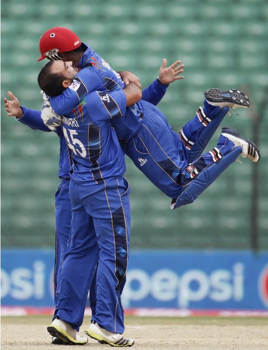 fghanistan's wicketkeeper Shahzad congratulates bowler Shenwari as he dismissed Pakistan's Maqsood successfully during their Asia Cup 2014 ODI cricket match in Fatullah