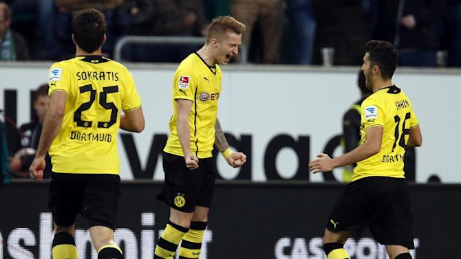 Dortmund's scorer Marco Reus, center, and his teammates Sokratis of Greece, left, and Nuri Sahin of Turkey, right, celebrate their side's first goal during the German first division Bundesliga soccer match between VfL Wolfsburg and Borussia Dortmund in Wolfsburg, Germany, Saturday, Nov. 9, 2013