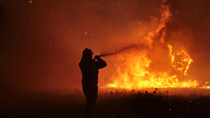 A firefighter works to extinguish a forest fire in Varibobi, a northwestern suburb of Athens, Tuesday, Aug. 6, 2013. A large wildfire raged through the suburb burning about four houses. No injuries were reported. (AP Photo/Michail Michailidis)
