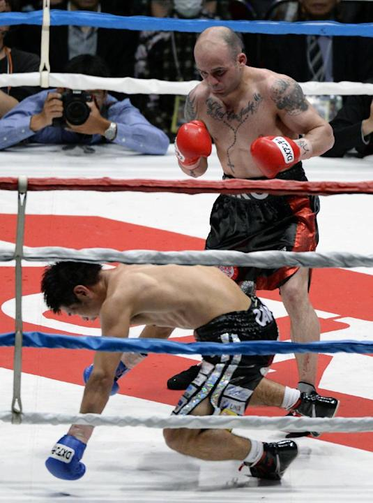 Spanish champion Kiko Martinez looks at Japanese challenger Hozumi Hasegawa kneeling down on the mat in the seventh round of their IBF super bantamweight boxing title bout in Osaka, western Japan, Wed