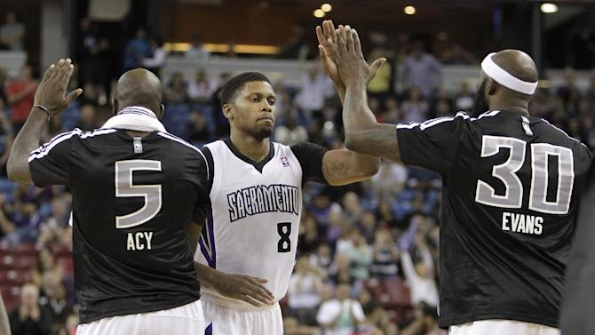 Sacramento Kings forward Rudy Gay, center, is congratulated by teammates Quincy Acy, left, and Reggie Evans as he walks to the bench during a timeout in overtime of an NBA basketball game against the Washington Wizards in Sacramento, Calif., Tuesday, March 18, 2014.  The Kings won in overtime 117-111