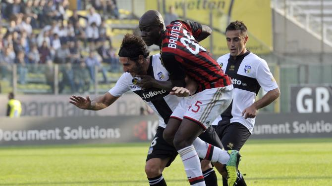 AC Milan's Balotelli fights for the ball with Parma's Lucarelli and Marchionni during their Italian Serie A soccer match at the Tardini stadium in Parma