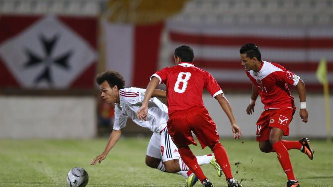 Denmark's Braithwaite fights for the ball with Malta's Briffa and Mintoff during their 2014 World Cup qualifying soccer match in Ta' Qali