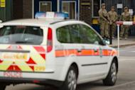 """A police car is parked outside the Royal Artillary Barracks, Headquarters Woolwich Station in Woolwich, east London, on May 22, 2013. British police shot and wounded two men after a man thought to be a serving soldier was killed outside a London barracks, in an attack Prime Minister David Cameron called """"truly shocking""""."""