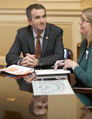 In this Jan. 26, 2016 photo, Virginia Lt. Gov. and Democratic candidate for governor, Ralph Northam, left, talks with Senate Chief Deputy Clerk Tara Perkinson before the start of a Senate session at the Capitol in Richmond, Va. In what sounds like an echo of 2016, governor's races this year in Virginia and New Jersey are being swept up in many of the same political currents that emerged during last year's turbulent presidential campaign. (AP Photo/Steve Helber)