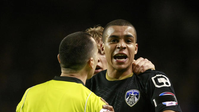 Oldham Athletic's Tom Adeyemi, right, is calmed by referee Neil Swarbrick during their FA Cup third round soccer match against Liverpool at Anfield, Liverpool, England, Friday Jan. 6, 2012. The police are investigating an incident in which a black Oldham player appeared to be the target of abuse from Liverpool fans during an FA Cup third-round match on Friday. Oldham right back Tom Adeyemi was visibly upset late in the game at Anfield after seemingly taking offence from something shouted from the Liverpool-supporting area known as The Kop.  (AP Photo/Tim Hales)