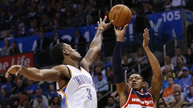 Washington Wizards guard Bradley Beal (3) shoots over Oklahoma City Thunder forward Perry Jones (3) in the first quarter of an NBA basketball game in Oklahoma City, Sunday, Nov. 10, 2013. Oklahoma City won 106-105 in overtime