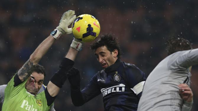 Chievo goalie Christian Puggioni, left, saves on a header of Inter Milan Argentine forward Diego Milito during a Serie A soccer match between Inter Milan and Chievo Verona, at the San Siro stadium in Milan, Italy, Monday, Jan.13, 2014