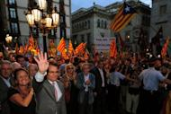 Catalonia's regional president Artur Mas (second left) and his wife Elena Rakosnic (left) wave to a crowd of supporters holding Catalan independence flags in Plaza Sant Jaume square in Barcelona on September 20. Spain's government announced Friday it will reform how the debt-struck regions are financed, a day after flatly rejecting Catalonia's bid for fiscal independence.