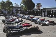 Inmates lie on the ground as riot policemen keep watch during an operation after a gunfight at the Tuxpan prison in Iguala, in the Mexican State of Guerrero January 3, 2014. REUTERS/Jesus Solano