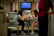 People eat as coverage of the London 2012 Olympics is shown on a television screen at a fast-food restaurant on August 2. The London Olympics had more viewers than any other event in US television history, broadcaster NBC said