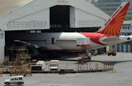 "An Air India passenger plane is parked at Chattrapati Shivaji International airport in Mumbai. At least 100 pilots from India's debt-laden national carrier Air India have failed to turn up to work on Tuesday in a move the civil aviation minister described as an ""illegal"" strike"
