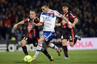 Lyon's forward Anthony Reveillere (C) fights for the ball with Nice's forward Eric Bautheac during their French L1 football match on December 22, 2012, at the Gerland stadium in Lyon. Lyon defeated Nice 3-0 on Saturday to go level with leaders Paris Saint-Germain on 38 points as Ligue 1 prepared to head into its winter hibernation