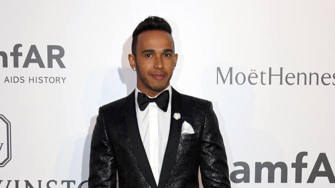 Formula One driver Lewis Hamilton poses during a photocall as he arrives to attend the amfAR's Cinema Against AIDS 2015 event during the 68th Cannes Film Festival in Antibes, near Cannes