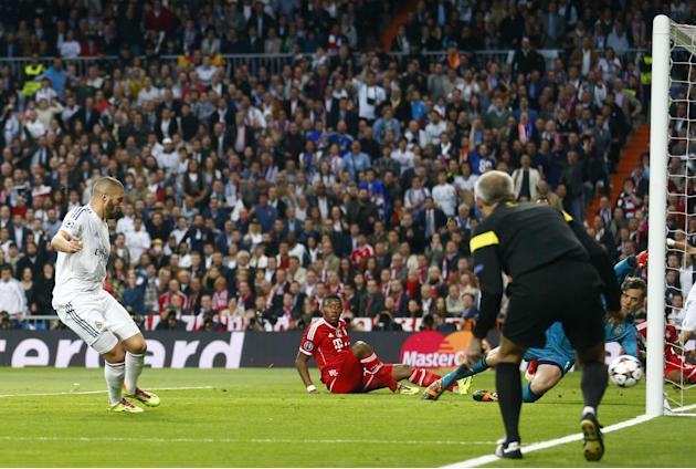 Real's Karim Benzema, left, scores the opening goal past Bayern goalkeeper Manuel Neuer, right during a  Champions League semifinal first leg soccer match between Real Madrid and Bayern Munich at