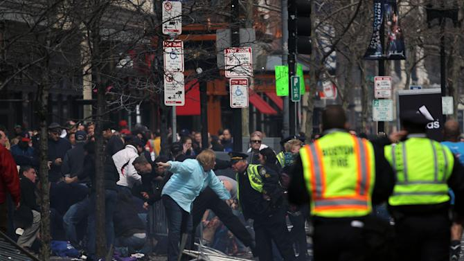 In this photo provided by The Daily Free Press and Kenshin Okubo, people react to an explosion at the 2013 Boston Marathon in Boston, Monday, April 15, 2013. Two explosions shattered the euphoria of the Boston Marathon finish line on Monday, sending authorities out on the course to carry off the injured while the stragglers were rerouted away from the smoking site of the blasts. (AP Photo/The Daily Free Press, Kenshin Okubo) MANDATORY CREDIT