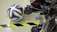 A 'Brazuca' football is seen next to an exoskeleton at Brazilian scientist Miguel Nicolelis' lab in Sao Paulo, Brazil, on January 1, 2014