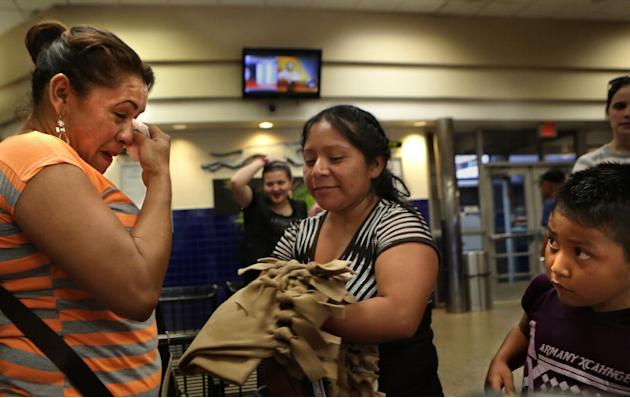 Yanira Lopez, left, wipes away tears after running into a friend from the Karnes County Detention Center at the San Antonio Greyhound bus on May 20, 2015 in San Antonio, Texas  The Interfaith Welcome