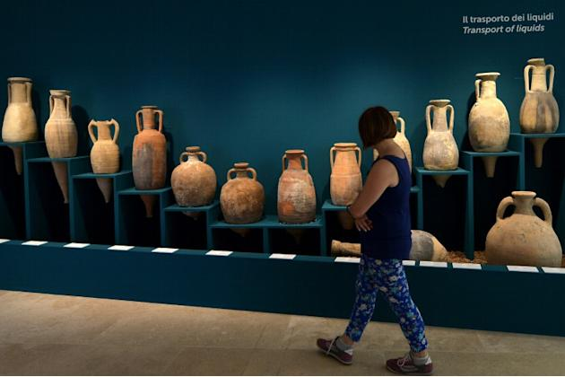 """A woman walks past amphorae used to transport liquids displayed during the exhibition """"Feeding the Empire: Tales of food from Rome and Pompei'' at Ara Pacis Museum in Rome on July 25, 201"""